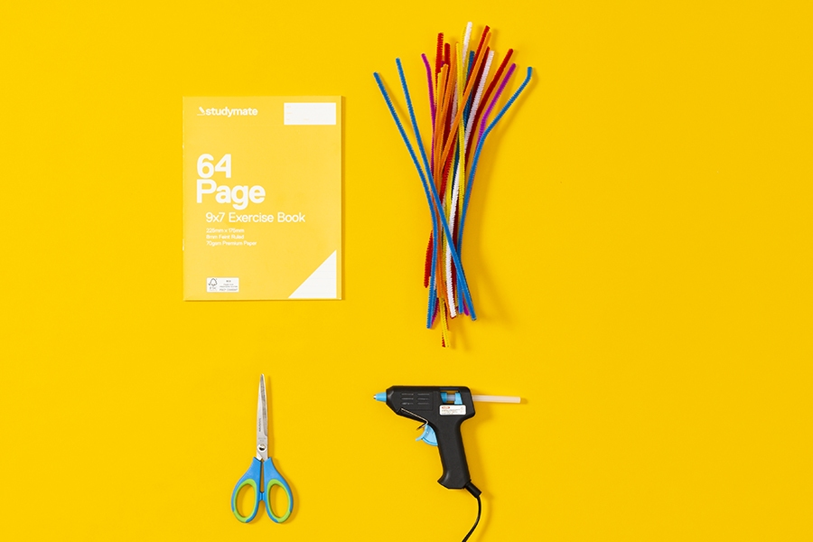 Kids craft supplies for making a DIY personalised school notebook with pipe cleaners.