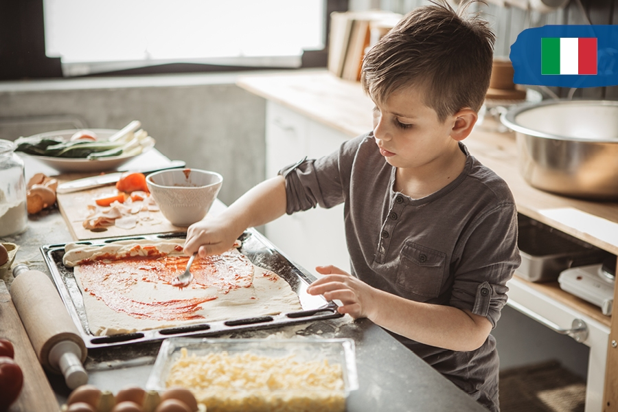 Kids can travel the world from home by cooking as an activity, like pizza for Italy.